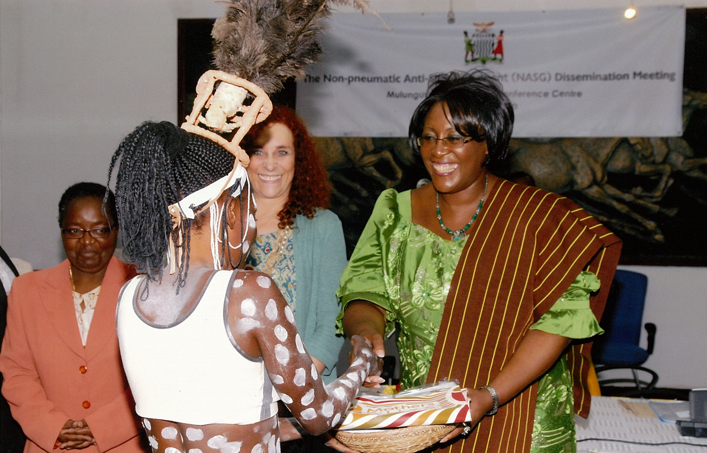 ZambiaFirst Lady, Dr. Christine Kaseba with Dr. Suellen Miller and traditional Zambian dancer at the meeting.